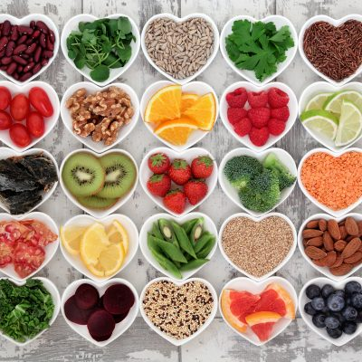 Diet detox super food selection in heart shaped porcelain bowls over distressed wooden background.
